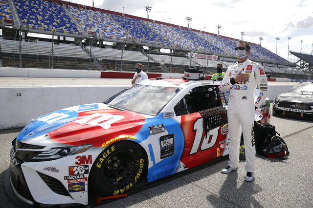Kyle Busch stands for the playing of the national anthem before the start of the NASCAR Cup Series auto race Sunday, May 17, 2020, in Darlington, S.C. (AP Photo/Brynn Anderson)