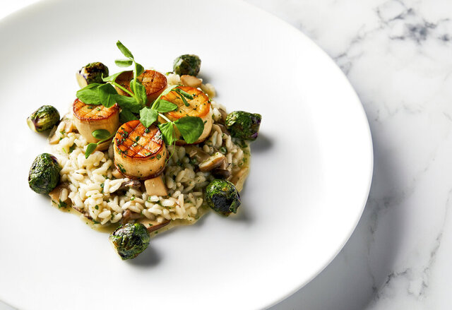 This image released by the Golden Globe Awards shows a dish of king oyster mushroom scallops on a bed of wild mushroom risotto with roasted Brussels sprouts, prepared by Beverly Hilton Executive Chef Matthew Morgan. The dish will be served at the Golden Globe Awards on Sunday. (Leslie Grow/Golden Globe Awards via AP)