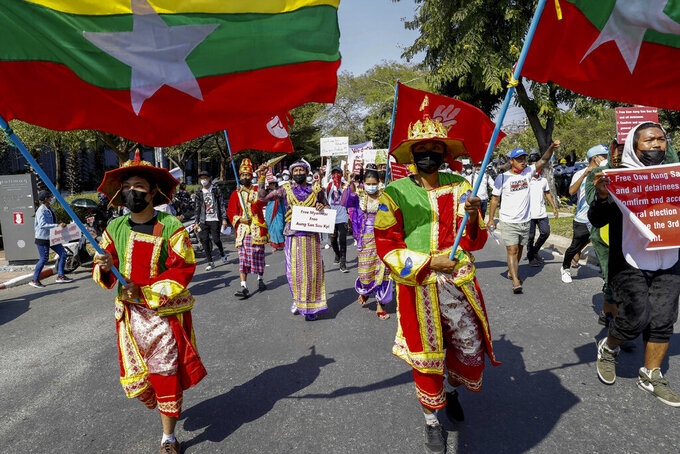 Demonstrators in traditional costumes march with national flags against the military coup during a protest in Mandalay, Myanmar on Thursday, Feb. 11, 2021. Large crowds demonstrating against the military takeover in Myanmar again defied a ban on protests Thursday, even after security forces ratcheted up the use of force against them and raided the headquarters of the political party of ousted leader Aung San Suu Kyi a day earlier. (AP Photo)