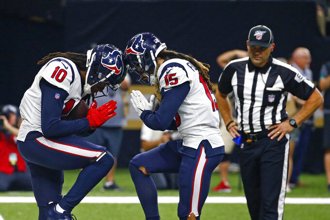 Houston Texans wide receiver DeAndre Hopkins (10) celebrates his second touchdown reception with wide receiver Will Fuller (15) in the second half of an NFL football game against the New Orleans Saints in New Orleans, Monday, Sept. 9, 2019. (AP Photo/Butch Dill)