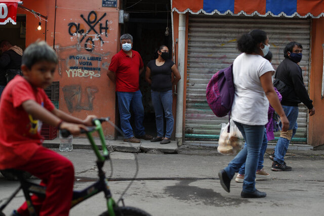 Jose Juan Serralde and his wife Blanca Evangelista Villada stand at the door to their home, located on a market street in San Gregorio Atlapulco, Xochimilco, Mexico City, Wednesday, July 29, 2020. Serralde's parents, who lived with the family, died from COVID-19 in May, and the couple and their four daughters then spent weeks quarantined at home, with most of them experiencing mild cases of COVID-19 before recovering. (AP Photo/Rebecca Blackwell)