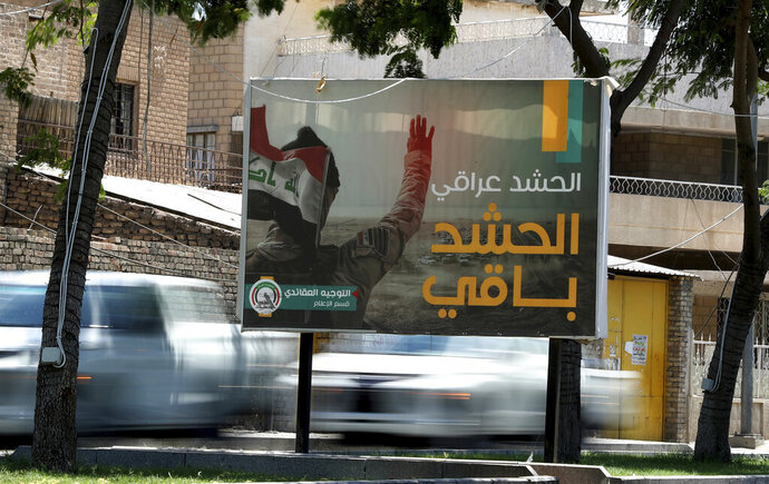 In this Tuesday, July 2, 2019 photo, motorists pass by a Popular Mobilization poster in Baghdad, Iraq. The Iraqi government's move to place Iranian-backed militias under the command of the armed forces is a political gamble by a prime minister increasingly caught in the middle of a dangerous rivalry between Iran and the U.S., the two main power brokers in Iraq. Facing pressure from the U.S. to curb the militias, the move allows Prime Minister Adel Abdul-Mahdi to portray a tough stance ahead of a planned visit to Washington. It is unlikely, though, that he would be able to rein in and neutralize Iran-supported groups and he risks coming off as a weak and ineffective leader if he doesn't. The Arabic sentence on the poster reads,