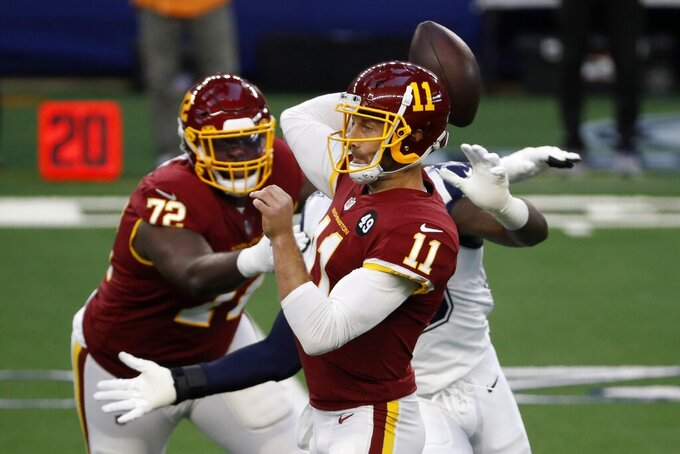 Washington Football Team quarterback Alex Smith (11) throws a pass as offensive tackle David Sharpe (72) helps against pressure from Dallas Cowboys defensive end Randy Gregory, rear, in the first half of an NFL football game in Arlington, Texas, Thursday, Nov. 26, 2020. (AP Photo/Roger Steinman)