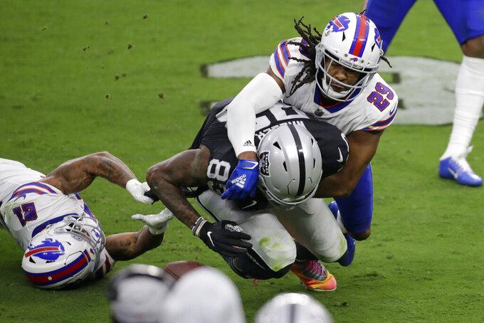Buffalo Bills cornerback Josh Norman (29) forces a fumble by Las Vegas Raiders tight end Darren Waller (83) during the second half of an NFL football game, Sunday, Oct. 4, 2020, in Las Vegas. (AP Photo/Isaac Brekken)
