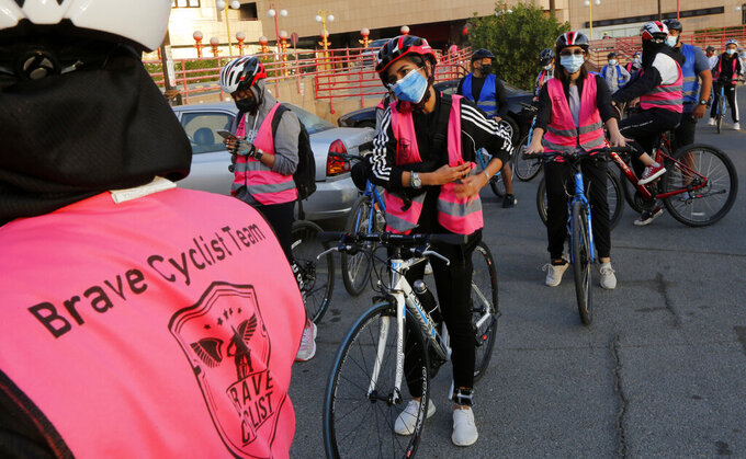 In this March 6, 2021 photo, members of the women's Brave Cyclist team prepare to start a tour in Jiddah, Saudi Arabia.  The Brave Cyclist team, which was formed in 2019 aiming to normalize the sport for women, organized a tour cycling ahead of International Women's Day. (AP Photo/Amr Nabil)
