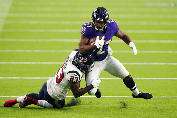 Baltimore Ravens running back J.K. Dobbins (27) is hit by Houston Texans strong safety Eric Murray (23) during the first half of an NFL football game Sunday, Sept.20, 2020, in Houston. (AP Photo/David J. Phillip)