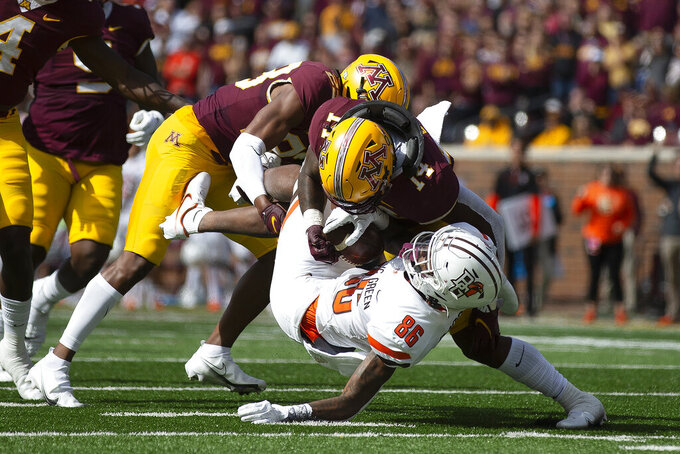Minnesota linebacker Braelen Oliver (14) tackles Bowling Green wide receiver Tyrone Broden (86) during the second half of an NCAA college football game Saturday, Sept. 25, 2021, in Minneapolis. Bowling Green won 14-10. (AP Photo/Stacy Bengs)