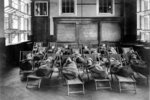 This 1911 photo from the Library of Congress shows children wrapped in blankets, at a fresh air class rest hour at Public School No. 51, in New York. Poor ventilation in school buildings across the U.S. will limit the ability of in-person instruction to resume safely. Some districts are warming to the idea of outdoor classrooms. (Library of Congress via AP)