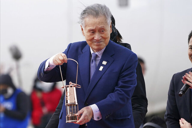 FILE - In this March 20, 2020, file photo, Tokyo 2020 Olympics chief Yoshiro Mori carries the Olympic flame during the Flame Arrival Ceremony at Japan Air Self-Defense Force Matsushima Base in Higashimatsushima in Miyagi Prefecture, north of Tokyo. Tokyo Olympic organizers seem to be leaning away from starting the rescheduled games in the spring of 2021. More and more the signs point toward the summer of 2021. Organizing committee President Mori suggested there would be no major change from 2020. (AP Photo/Eugene Hoshiko, File)