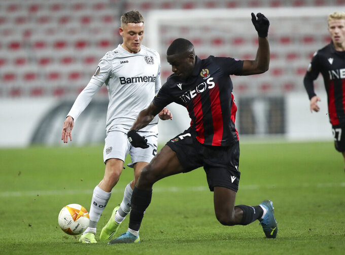 Leverkusen's Florian Wirtz, left, has his shot blocked by Nice's Stanley Nsoki, right, during the Europa League Group C soccer match between Nice and Bayer Leverkusen at the Allianz Riviera stadium in Nice, France, Thursday, Dec. 3, 2020. (AP Photo/Daniel Cole)