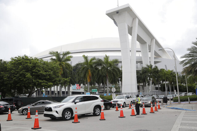 Vehicles wait in line outside of Marlins Park at a COVID-19 testing site during the coronavirus pandemic, Monday, July 6, 2020, in Miami. The long line of cars each morning as players arrive at work provides a reminder of the risks when they leave. Behavior away from the ballpark will be a big factor in determining whether Major League Baseball's attempt to salvage the 2020 season can succeed. (AP Photo/Lynne Sladky)