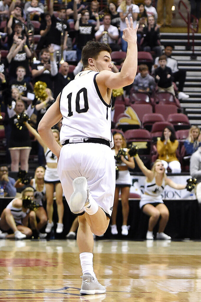 Wofford guard Nathan Hoover (10) signals a 3-point basket after scoring in the first half of an NCAA college basketball game for the Southern Conference basketball tournament championship, Saturday, March 9, 2018, in Asheville, N.C. Wofford won 99-72 over VMI. (AP Photo/Kathy Kmonicek)