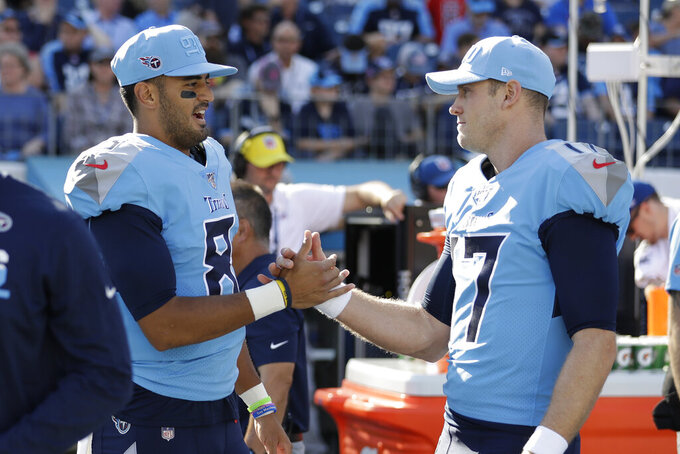 FILE — In this Oct. 20, 2019, file photo, Tennessee Titans quarterbacks Marcus Mariota (8) and Ryan Tannehill (17) shake hands before the team's NFL football game against the Los Angeles Chargers in Nashville, Tenn. Mariota was benched in mid-October, but he remains valuable to the team mimicking Tom Brady, Lamar Jackson and now Patrick Mahomes in practice for the AFC championship. He's also popped up in three straight games, completing a pass in two and going out for a pass in the last. (AP Photo/James Kenney, File)
