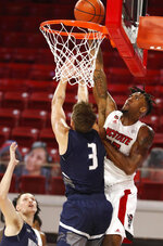 North Carolina State's Manny Bates (15) dunks over North Florida's Carter Hendricksen (3) during the first half  of an NCAA college basketball game in Raleigh, N.C., Friday, Nov. 27, 2020. (Ethan Hyman/The News & Observer via AP, Pool)