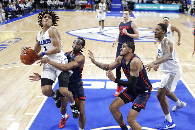 Saint Louis' Yuri Collins, left, heads to the basket as Dayton's Rodney Chatman, second from left, and Obi Toppin defend during the first half of an NCAA college basketball game Friday, Jan. 17, 2020, in St. Louis. (AP Photo/Jeff Roberson)