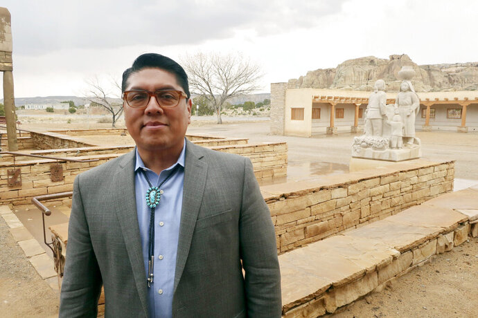 "FILE - In this March 21, 2019 file photo, Acoma Pueblo Gov. Brian Vallo poses outside the Pueblo's cultural center about 60 miles west of Albuquerque, New Mexico. A ceremonial shield at the center of a yearslong international debate over exporting of sacred Native American objects to foreign markets has returned to New Mexico. U.S. and Acoma Pueblo officials planned Monday, Nov. 18 to announce the shield's return from Paris, where it had been listed for bidding in 2016 before the EVE auction house took the rare step of halting its sale. ""It will be a day of high emotion and thanksgiving,"" Vallo said ahead of the shield's expected return to his tribe.  (AP Photo/Felicia Fonseca, File)"