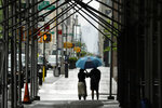 FILE - In this May 23, 2020, file photo pedestrians use an umbrella to protect themselves from the rain as they walk along Sixth Avenue during the coronavirus pandemic in New York. As some parts of the nation continue to ease stay-at-home orders meant to slow the spread of the coronavirus, the economy remains in free fall. (AP Photo/Frank Franklin II, File)