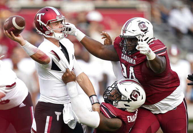 Troy quarterback Taylor Powell, left, is tackled by South Carolina defensive end Kingsley Enagbare, center, in the second half of an NCAA college football game Saturday, Oct. 2, 2021, in Columbia, S.C. (AP Photo/Brynn Anderson)