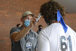 Michael Toth, athletic trainer, left, takes Gavin Guers' temperature before football practice at Blue Mountain High School in Orwigsburg, Pa., on Monday, Aug. 24, 2020. (Lindsey Shuey/The Republican-Herald via AP)