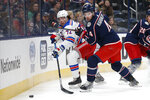 New York Rangers' Filip Chytil, left, of the Czech Republic, passes the puck past Columbus Blue Jackets' Scott Harrington during the first period of an NHL hockey game Friday, Feb. 14, 2020, in Columbus, Ohio. (AP Photo/Jay LaPrete)