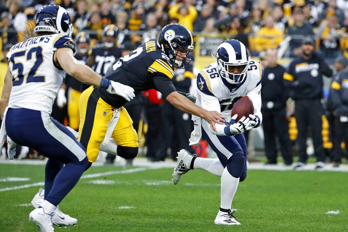 Los Angeles Rams defensive end Dante Fowler (56) recovers a fumble in front of Pittsburgh Steelers quarterback Mason Rudolph (2) and returns it for a touchdown during the first half of an NFL football game in Pittsburgh, Sunday, Nov. 10, 2019. (AP Photo/Don Wright)