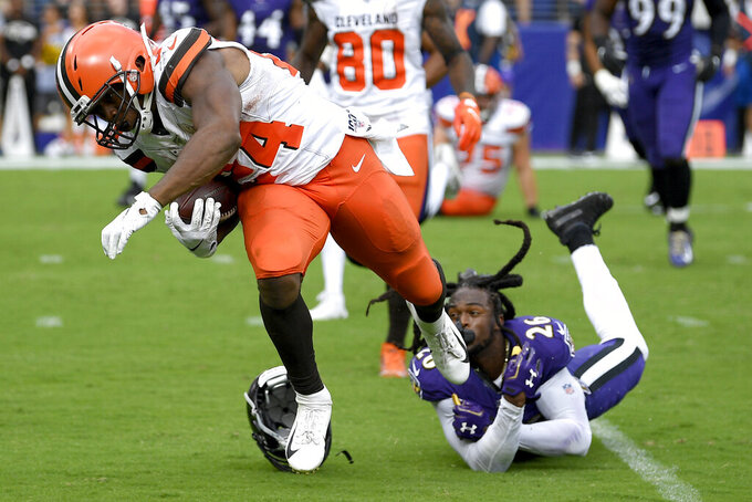 Cleveland Browns running back Nick Chubb (24) avoids a tackle by Baltimore Ravens cornerback Maurice Canady (26) while running for a touchdown during the second half of an NFL football game Sunday, Sept. 29, 2019, in Baltimore. (AP Photo/Nick Wass)