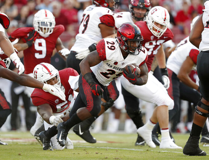San Diego State running back Juwan Washington (29) breaks a tackle against Stanford defensive end Jovan Swann (51) during the first half of an NCAA college football game Friday, Aug. 31, 2018, in Stanford, Calif. (AP Photo/Tony Avelar)