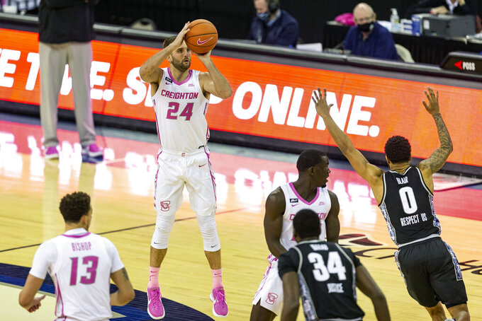 Creighton guard Mitch Ballock (24) makes a three point shot against Georgetown guard Jahvon Blair (0) in the first half during an NCAA college basketball game Wednesday, Feb. 3, 2021, in Omaha, Neb. (AP Photo/John Peterson)