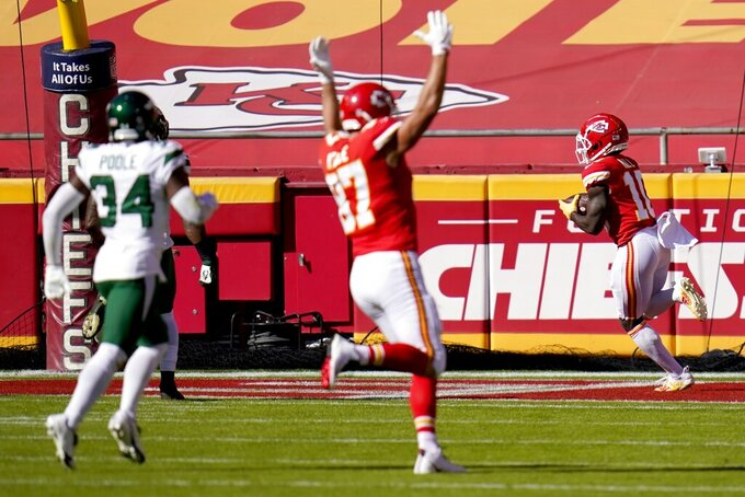 New York Jets cornerback Brian Poole (34) looks on as Kansas City Chiefs' Travis Kelce (87) celebrates after Tyreek Hill, right, caught a touchdown pass in the first half of an NFL football game on Sunday, Nov. 1, 2020, in Kansas City, Mo. (AP Photo/Jeff Roberson)