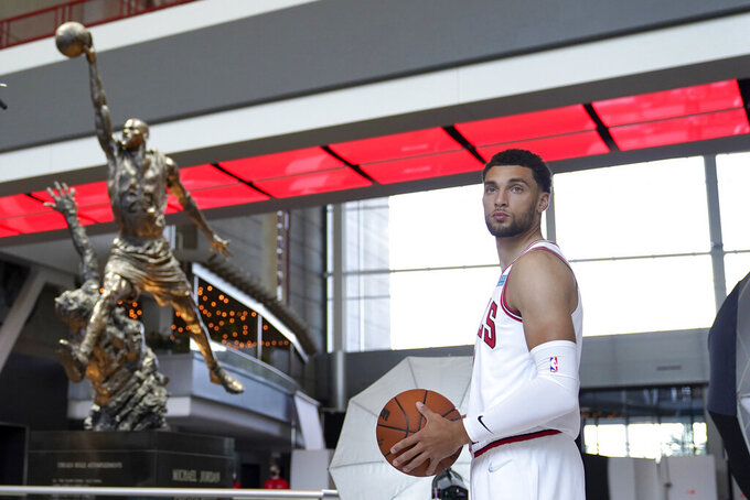 Chicago Bulls' Zach LaVine looks out a window near the Michael Jordan statue in the atrium of the United Center during the Bulls' NBA basketball media day Monday, Sept. 27, 2021, in Chicago. (AP Photo/Charles Rex Arbogast)