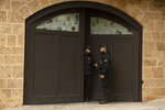 Private security guards confer at the garage door of the house of ex-Nissan chief Carlos Ghosn in Beirut, Lebanon, Tuesday, Jan. 7, 2020. Tokyo prosecutors obtained an arrest warrant Tuesday for the wife of Nissan's former chairman, Ghosn, on suspicion of perjury, adding to the couple's legal troubles in the country where he once was revered as a star executive. (AP Photo/Maya Alleruzzo)