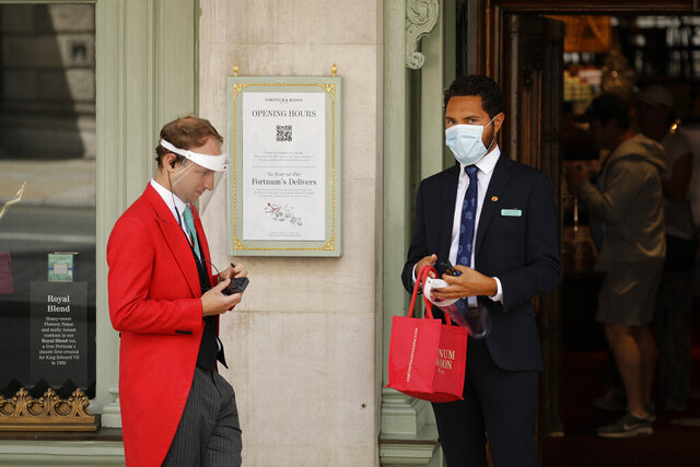 A doorman wearing a face shield to protect from coronavirus stands with a colleague at the main entrance of the Fortnum & Mason department store in the Piccadilly area of central London, Friday, May 22, 2020. The store reopened its food hall department for customers to enter yesterday as part of a phased reopening as the British government is beginning to relax aspects of its nationwide coronavirus lockdown. (AP Photo/Matt Dunham)