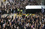 In this Oct. 9, 2019, photo, supporters surround a police bus carrying political activist Edward Leung as it leaves the High Court in Hong Kong. Several hundred masked protestors chanting for revolution have gathered at Hong Kong's High Court for the appeal hearing of an activist sentenced to six years in prison for his part in a violent nightlong clash with police. (AP Photo/Vincent Yu, File)