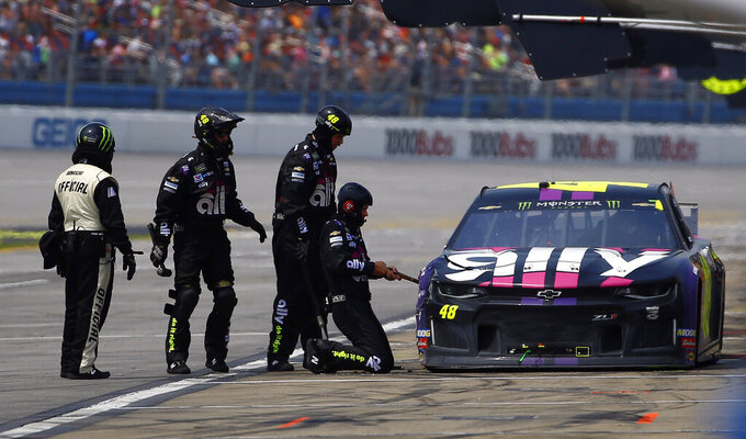 Crew members for Jimmie Johnson (48) work on his car after it hit the outside wall during a NASCAR Cup Series auto race at Talladega Superspeedway, Sunday, April 28, 2019, in Talladega, Ala. (AP Photo/Butch Dill)