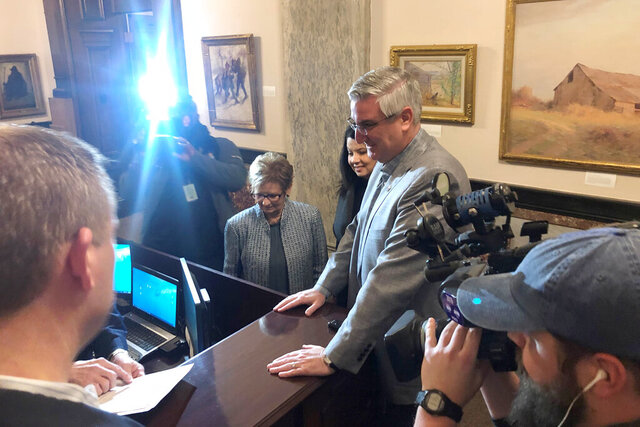 Indiana Gov. Eric Holcomb stands with his wife, Janet Holcomb, center, and Indiana Secretary of State Connie Lawson, left, as he formally files paperwork to seek a second term in the 2020 election on Tuesday, Jan. 21, 2020, at the Secretary of State's office in Indianapolis. (AP Photo/Tom Davies)