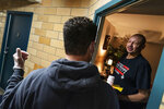Michael J. DeBritto, 65, right, receives a Thanksgiving dinner from Meals on Wheels volunteer, Ted Fischer, Wednesday, Nov. 25, 2020, at his home in Providence, R.I. As more at-risk seniors find themselves unable to leave their homes during the COVID pandemic, Meals on Wheels has been delivering on average 4,000 meals per day up from their pre-pandemic average of 1200. (AP Photo/David Goldman)
