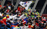Fans wave flags during the women's luge final at the 2018 Winter Olympics in Pyeongchang, South Korea, Tuesday, Feb. 13, 2018. (AP Photo/Andy Wong)