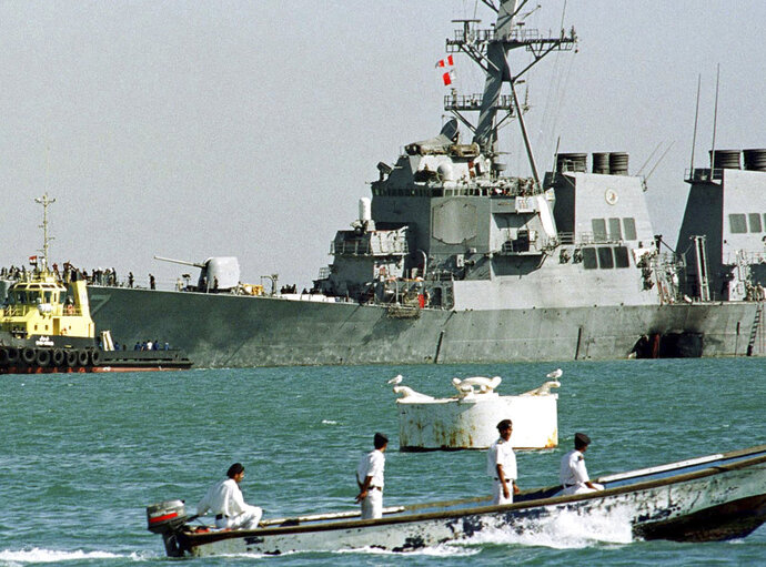 FILE - In this Oct. 29, 2000, file photo, a Yemeni police boat passes by the stricken USS Cole as it is pulled out of Aden port by Yemeni tugboats to deep water after an al-Qaida suicide attack in Aden, Yemen. Yemen's yearslong war between Shiite rebels and a Saudi-led coalition backing its exiled government has escalated with an assault on the insurgent-held port city of Hodeida. (AP Photo/Hasan Jamali, File)