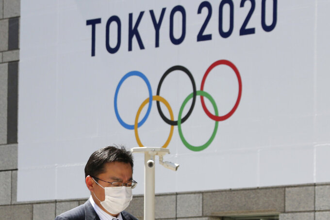FILE - In this March 25, 2020, file photo, a man walks in front of a Tokyo Olympics logo at the Tokyo metropolitan government headquarters building in Tokyo. At least 70% of U.S. Olympic sports organizations have applied for government loans in the wake of the coronavirus pandemic, a chilling figure that underscores the frailties embedded within the world's most dominant Olympic sports system.  (AP Photo/Koji Sasahara, File)