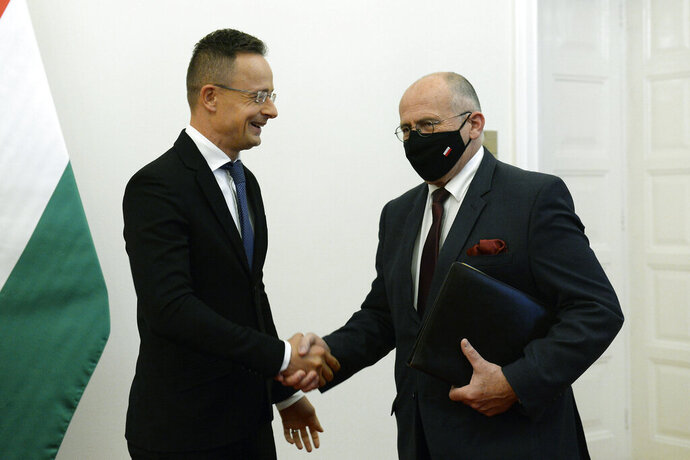 Hungarian Minister of Foreign Affairs and Trade Peter Szijjarto, left, receives his Polish counterpart, Zbigniew Rau in the Ministry of Foreign Affairs and Trade in Budapest, Hungary, Monday, Sept. 28, 2020. (Lajos Soos/MTI via AP)