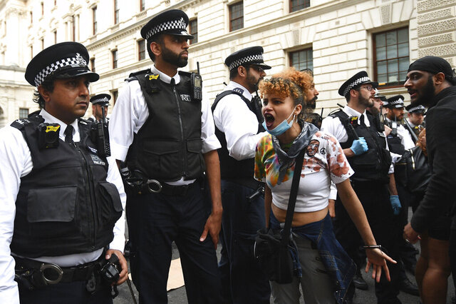 Police officers form a line to block protesters in central London on Wednesday, June 3, 2020 after a demonstration over the death of George Floyd, a black man who died after being restrained by Minneapolis police officers on May 25. Protests have taken place across America and internationally, after a white Minneapolis police officer pressed his knee against Floyd's neck while the handcuffed black man called out that he couldn't breathe. The officer, Derek Chauvin, has been fired and charged with murder. (Yui Mok/PA via AP)