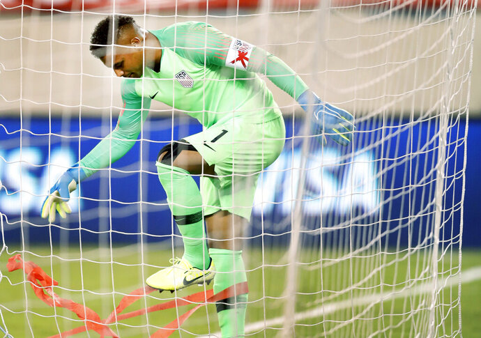 U.S. goalkeeper Zack Steffen (1) untangles red streamers from his legs after fans showered the field with them when Mexico scored a goal during the second half of an international friendly soccer match Friday, Sept. 6, 2019, in East Rutherford, N.J. Mexico won 3-0. (AP Photo/Kathy Willens)