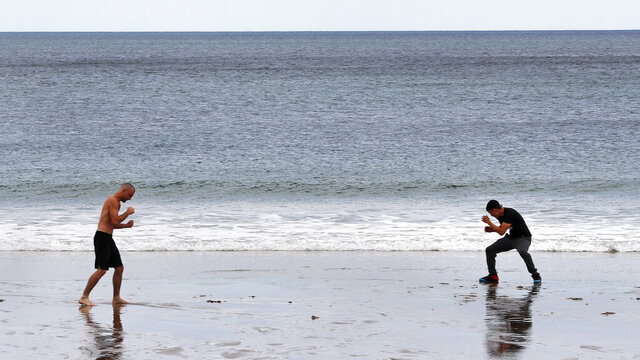 MMA fighter Chris Caterino, left, and boxer Jimmy Laboy train at a social distance along the shore of Salisbury Beach, Monday, June 1, 2020, in Salisbury, Mass. Beachgoers are restricted to keep more than six feet apart due to the COVID-19 outbreak. (AP Photo/Charles Krupa)