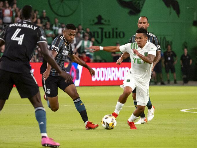 Austin FC midfielder Daniel Pereira, right, drives toward the goal against LA Galaxy midfielder Rayan Raveloson, left, during the first half of an MLS soccer match, Sunday, Sept. 26, 2021, in Austin, Texas. (AP Photo/Michael Thomas)