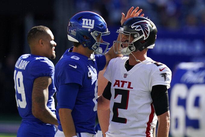 New York Giants quarterback Daniel Jones, left, and Atlanta Falcons quarterback Matt Ryan, right, meet on the field after an NFL football game, Sunday, Sept. 26, 2021, in East Rutherford, N.J. The Falcons won 17-14. (AP Photo/Seth Wenig)