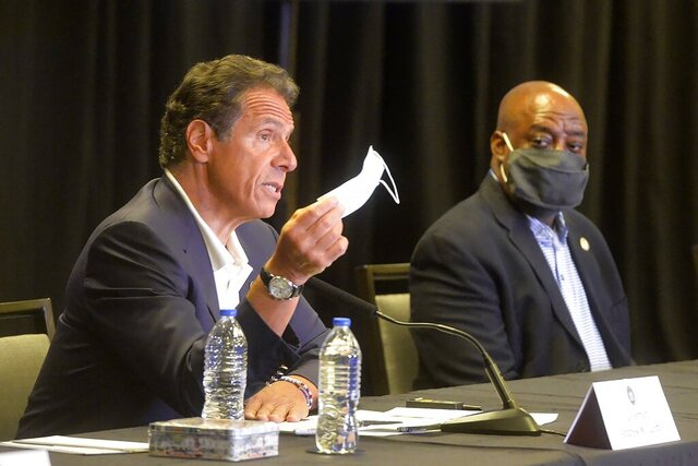 New York Gov. Andrew Cuomo waves a mask to make a point during a news conference at the Hyatt, in Savannah, Ga. on Monday, July 20, 2020. Listening in is Savannah Mayor Van Johnson. (Steve Bisson/Savannah Morning News via AP)
