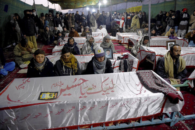 People from the Shiite Hazara community gather around coffins of coal mine workers killed by gunmen near the Machh coal field, during a sit-in to protest, in Quetta, Pakistan, Friday, Jan. 8, 2021. Pakistan's prime minister Friday appealed the protesting minority Shiites not to link the burial of 11 coal miners from Hazara community who were killed by the Islamic State group to his visit to the mourners, saying such a demand amounted to blackmailing the country's premier. (AP Photo/Arshad Butt)