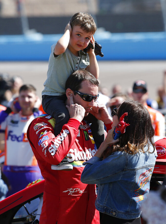 Kyle Busch, with his son Brexton and wife Samantha, protect their ears from the sound of a flyby of two F-35 fighter jets prior to the start of the NASCAR Cup Series auto race at ISM Raceway, Sunday, March 10, 2019, in Avondale, Ariz. (AP Photo/Ralph Freso)