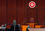 Security from the Legislative Council guard and disinfect after a pro-democracy lawmaker hurled an object during the second day of debate on a bill that would criminalize insulting or abusing the Chinese anthem in Hong Kong, Thursday, May 28, 2020. The lawmaker ejected later had spilled a substance on the floor that had to be cleaned up by firefighters wearing protective gear.(AP Photo/Vincent Yu)