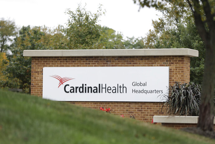 A sign is displayed at the Cardinal Health, Inc. corporate office Wednesday, Oct. 16, 2019, in Dublin, Ohio. Shares of big drug distributors soared Wednesday on word of a potential settlement ahead of the first federal trial over the opioid crisis. Two people with knowledge of the negotiations, which have lasted months, confirmed to The Associated Press that McKesson Corp., AmerisourceBergen Corp., and Cardinal Health, Inc., have offered $18 billion over 18 years to settle more than 2,000 lawsuits across the country. (AP Photo/Darron Cummings)